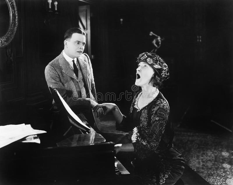 Man looking in horror at a singing woman. (All persons depicted are no longer living and no estate exists. Supplier grants that there will be no model release royalty free stock images