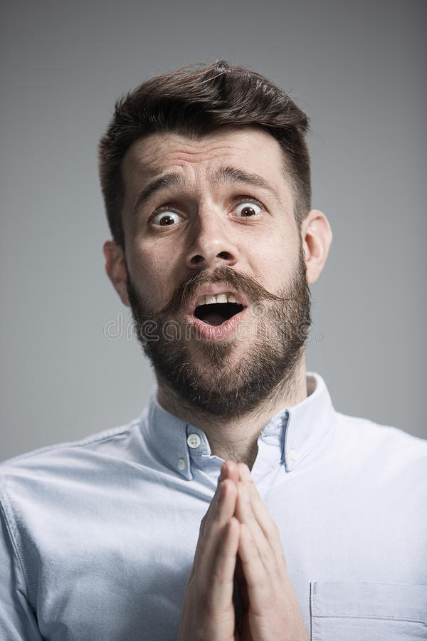 Man is looking imploring over gray background stock photo