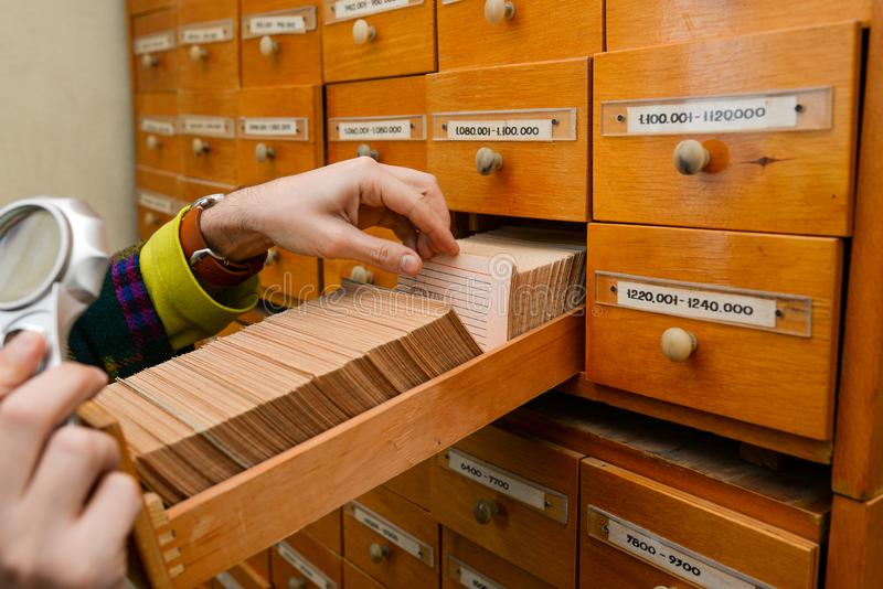 A man is looking for information in a box with paper cards. Search for data and information. Data storage in the library. Or in the office. Database royalty free stock images