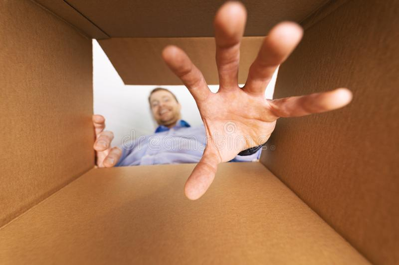 Man looking inside the box and reaching for goods stock image