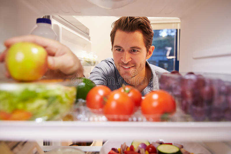 Man Looking Inside Fridge Full Of Food And Choosing Apple royalty free stock image