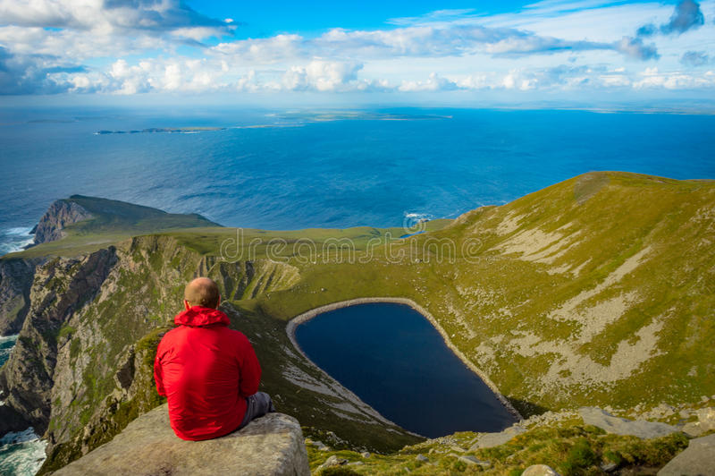 Man looking at a lake in a hill on Achill island, Co. Mayo. stock photography