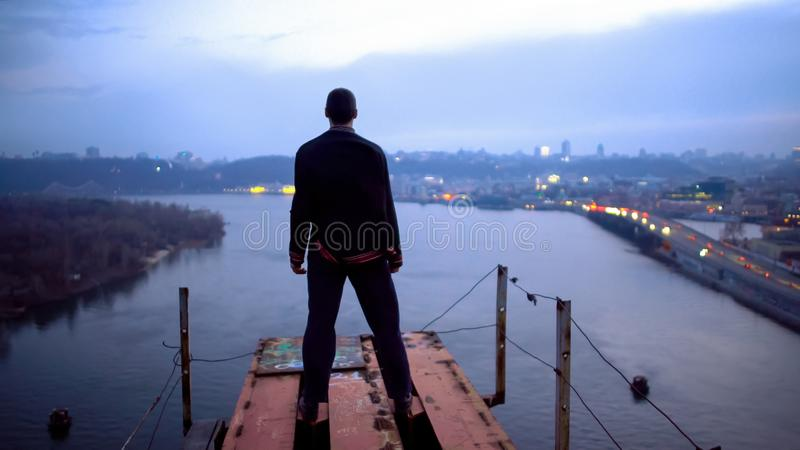 Man looking at lights of city standing on edge of unfinished bridge, inspiration stock image