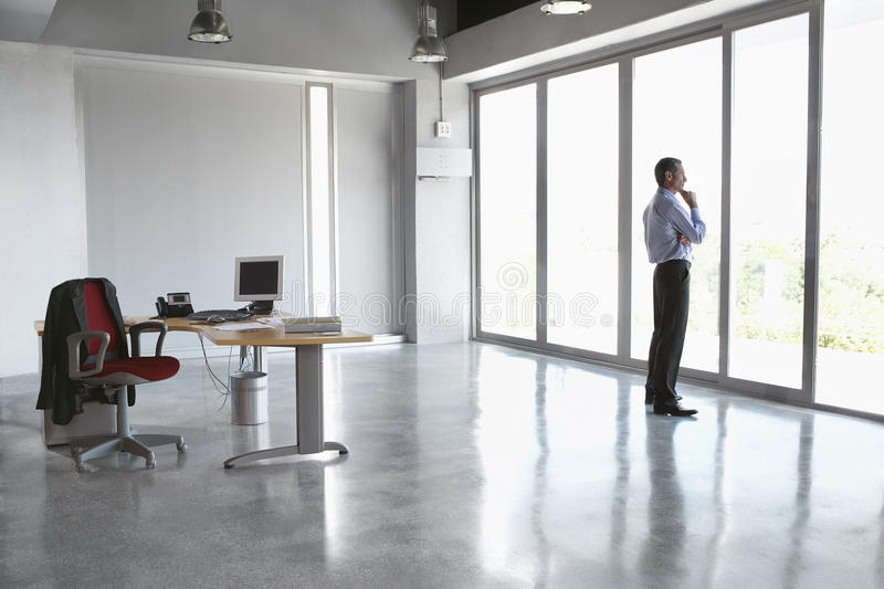 People On Sides Of Door : Man looking out of glass door in empty office stock photo