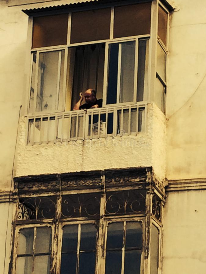 Morocco Man on balcony of old building stock photos