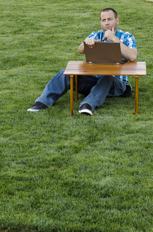 Man looking out with a lap top at a picnic table. Man looking out thinking with a laptop in front of him outdoors sitting at a picnic table in the grass royalty free stock photography