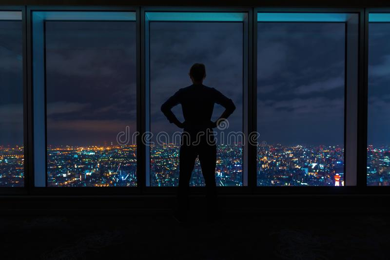 Man looking out large windows high above a sprawling city royalty free stock photo