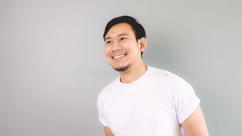 A man looking out and smile. An asian man with white t-shirt and grey background stock photography