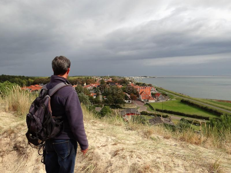 Man looking over  Vlieland from a top of a dune royalty free stock photography