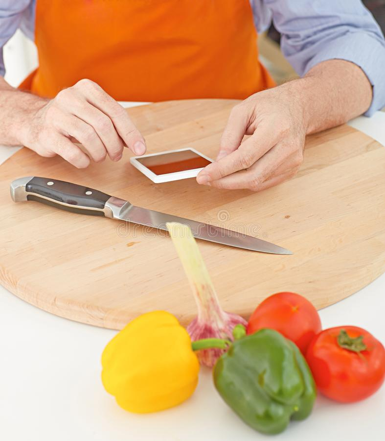 Mature man looking for a recipe of fresh vegetables on the internet on his phone. Man looking for a recipe of fresh vegetables on the internet on his phone stock photo