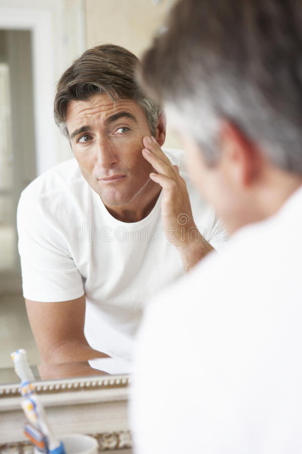 Man Looking At Reflection In Bathroom Mirror royalty free stock image