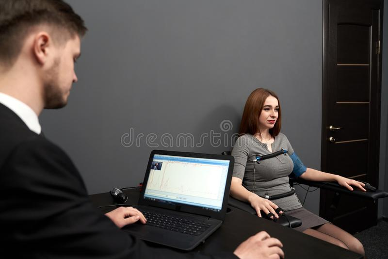 Man looking at screen of polygraph and monitoring . Concentrated women sitting in grey room, testing at computer polygraph. Young men sitting at table and royalty free stock image