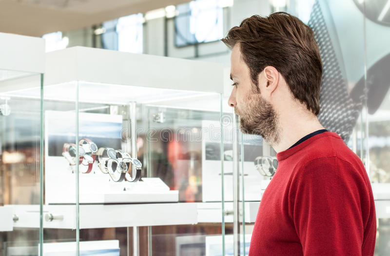 Man looking at shop window or display case in shopping center stock photography
