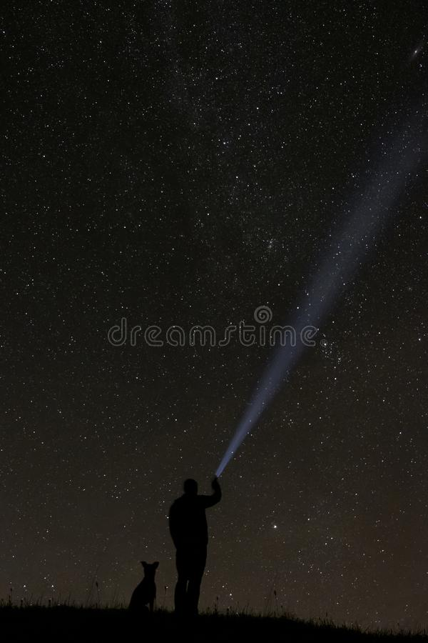 Man looking at the stars with his dog royalty free stock photo