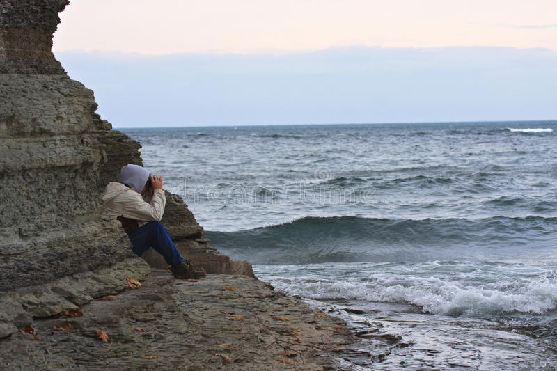 Man Looking at Stormy Sea. Man sitting on a rocky shore looking out at stormy seas with binoculars on a dull gray autumn day in November royalty free stock photography
