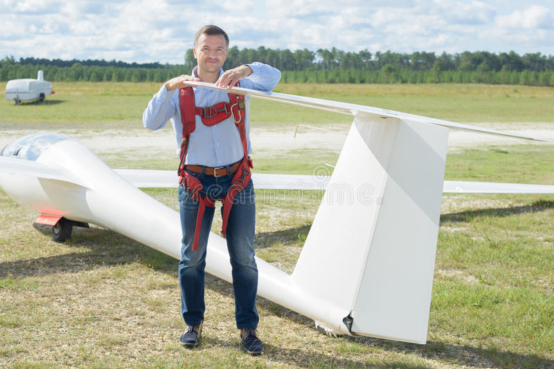 Man looking at tailpiece glider. Man looking at tailpiece of glider royalty free stock photos