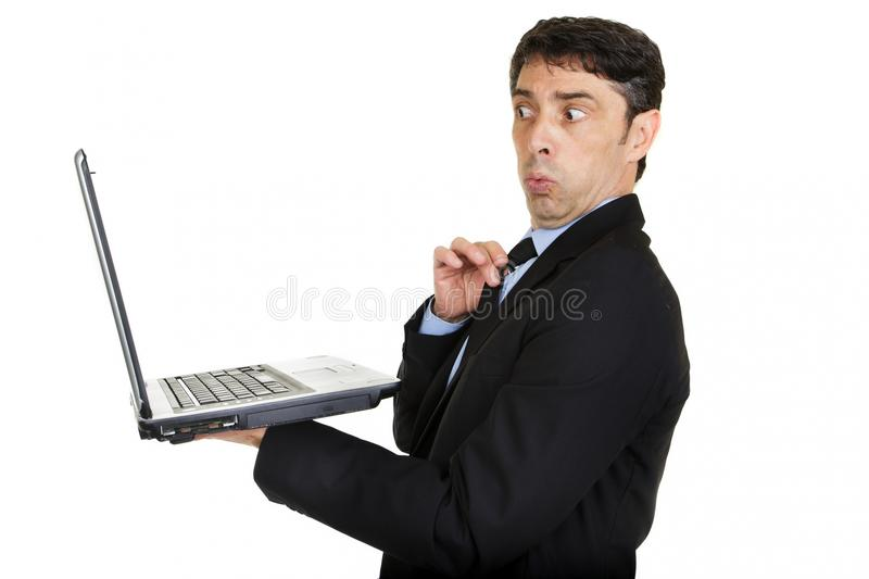 Man looking taken aback. And affronted as he looks at the screen of his handheld laptop computer and sees something risque or offensive isolated on white royalty free stock image