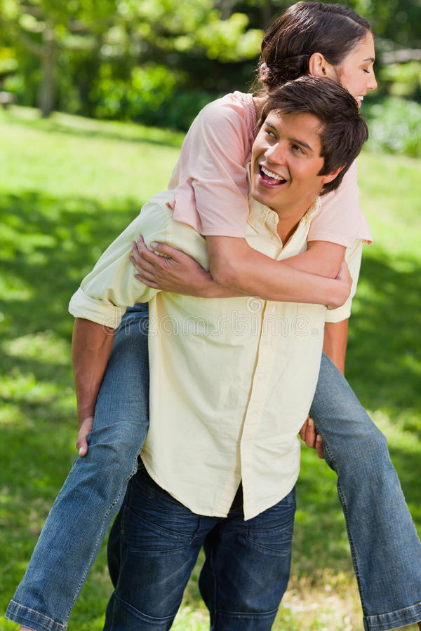 Man Looking To His Side While Carrying His Friend On His Back Stock Images