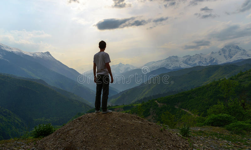 The man looking to the majestic mountais view. The man looking on the rock to the majestic mountais view royalty free stock images