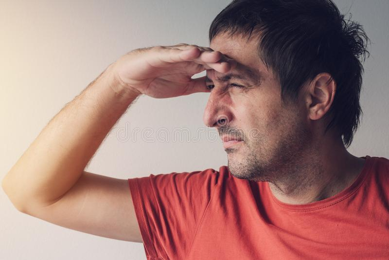 Man looking towards the bright light source. Optimistic concept of new chance, hope and solutions of problems stock image