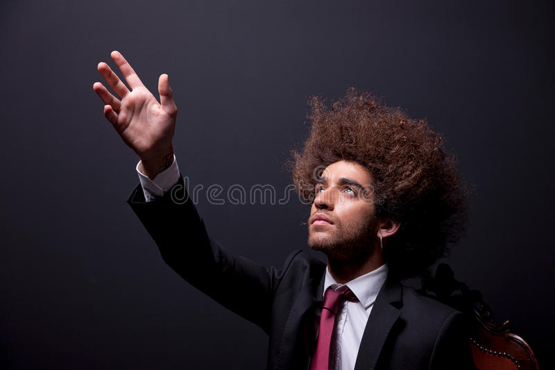 Man  Looking Up To The Light, Arm Raised- Sign Of Stock Photography