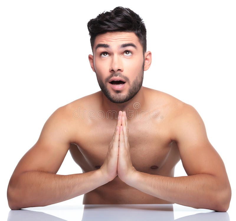 Man is looking up to something while praying. Amazed young man is looking up to something while praying royalty free stock photo