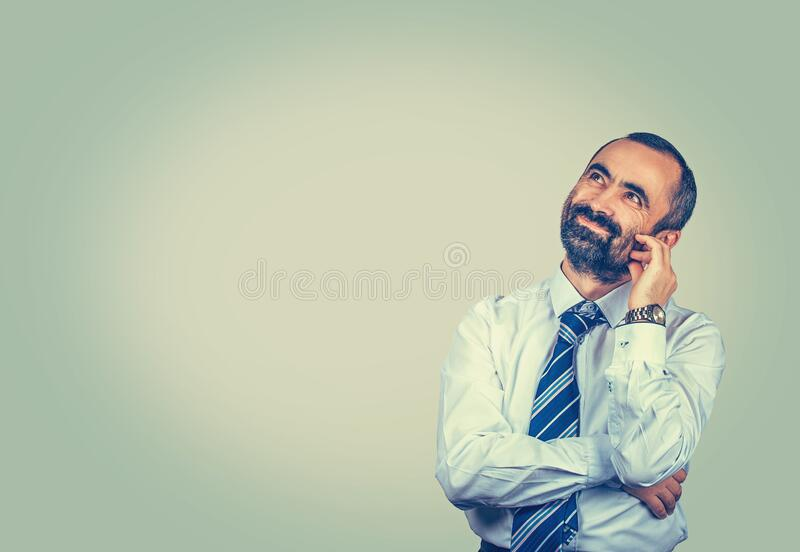 Man looking up touch face with fingers daydreaming about future. Daydreaming. Smiling isolated elegant bearded man looking up touch face with fingers having a royalty free stock photography
