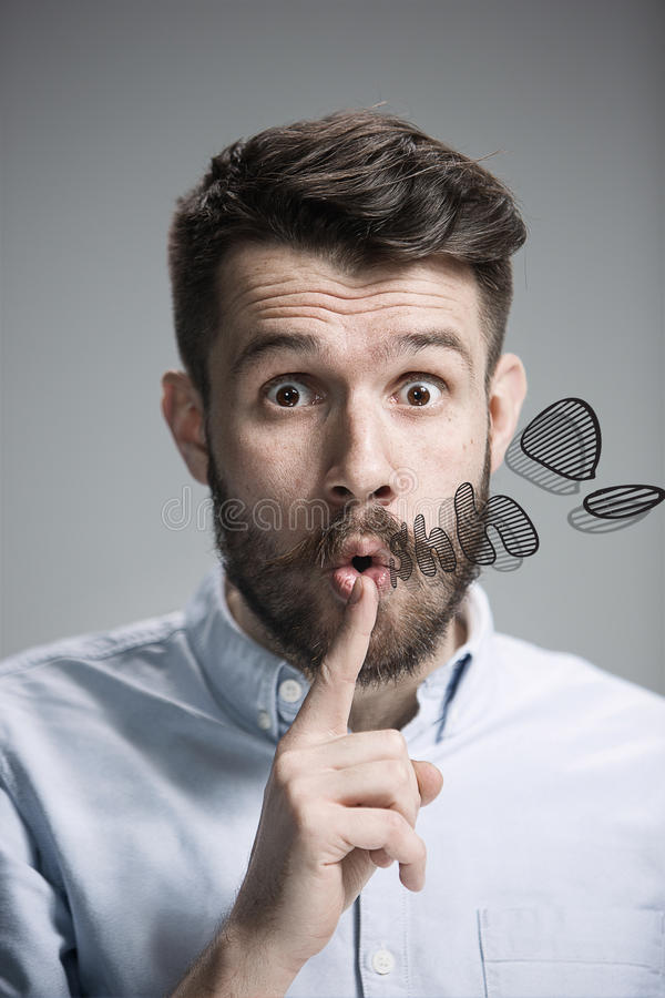 Man is looking wary. Over gray background. Man wearing a blue shirt is looking wary and saying Shh. Over gray background stock photo
