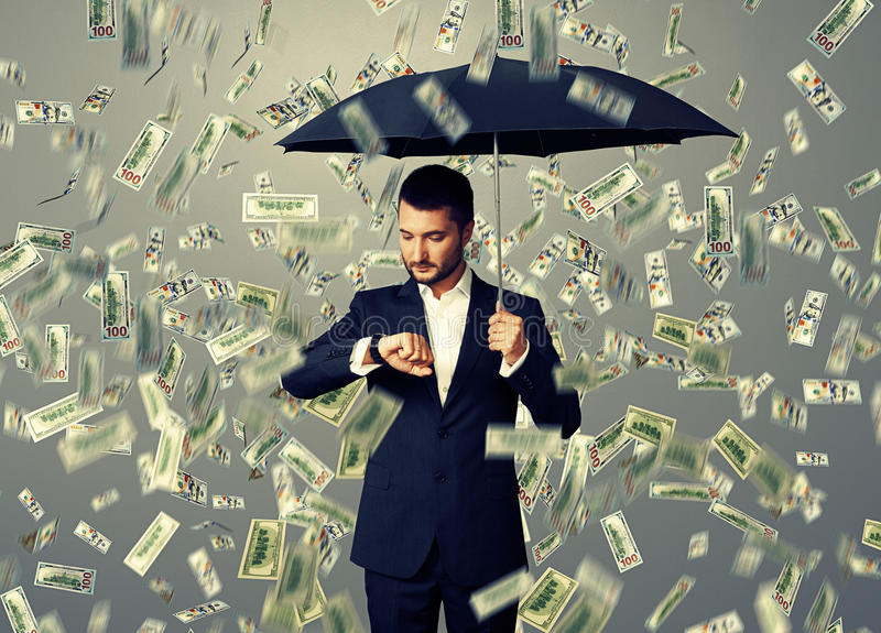 Man looking at watch. Young businessman with black umbrella standing under money rain and looking at watch royalty free stock image