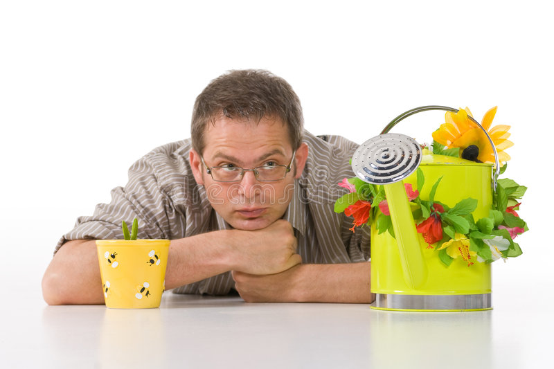 Man looking at water can. A studio view of a man lying on the floor beside a small potted plant, staring at a nearby watering can royalty free stock photo