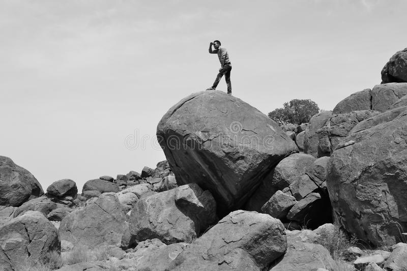 Man looking for the way in the desert -B&W-. Man standing on a pile of rocks, may be he lost the way royalty free stock photography