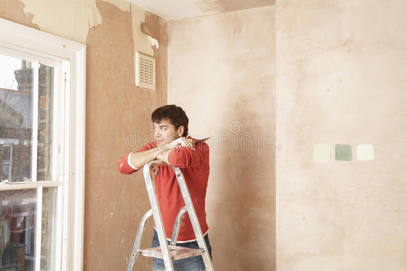 Man Looking Through Window While Resting On Step Ladder royalty free stock photos