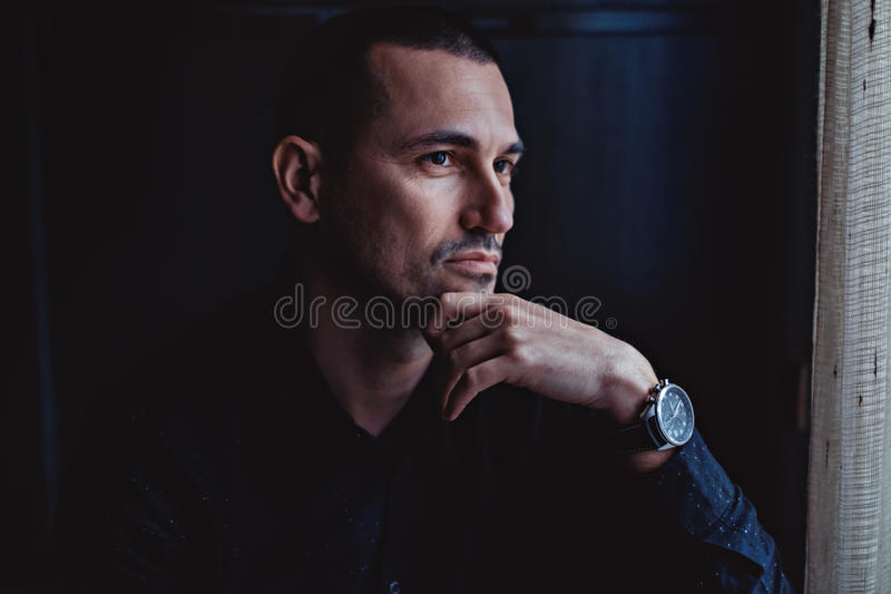 Man looking through window and thinking royalty free stock photo