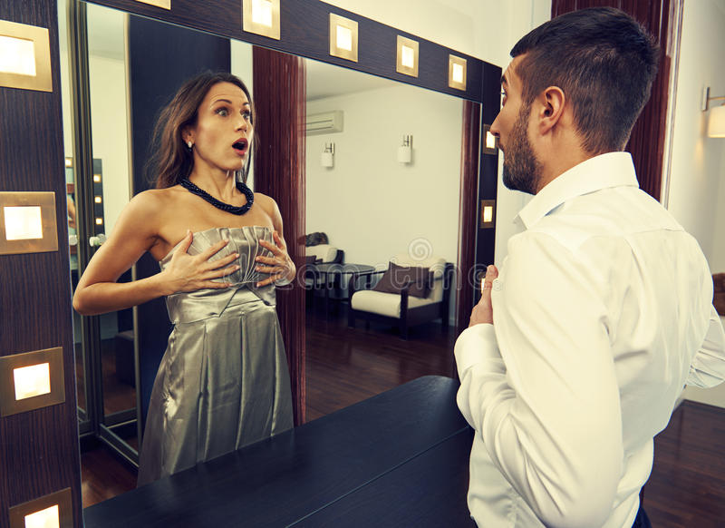 Man looking at woman in the mirror. Frightened men looking at women in the mirror royalty free stock image