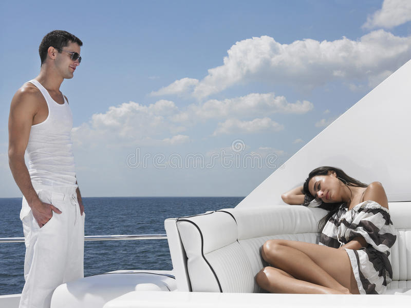 Man Looking At Woman Sleeping On Sofa In Yacht stock photography