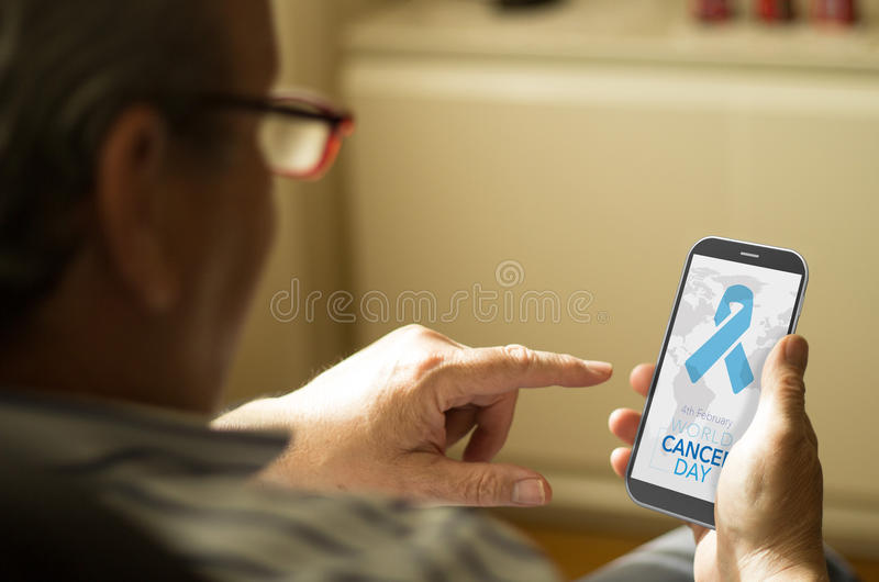 Man looking World Cancer Day graphic on a smartphone. Business concept: man with World Cancer Day background on screen phone at home. All screen graphics are royalty free stock image