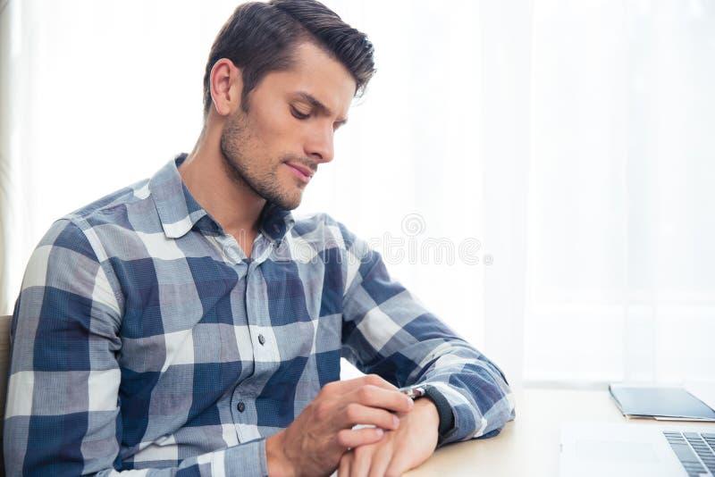 Man looking on wrist watc. Portrait ofa young man looking on wrist watch at home royalty free stock photos