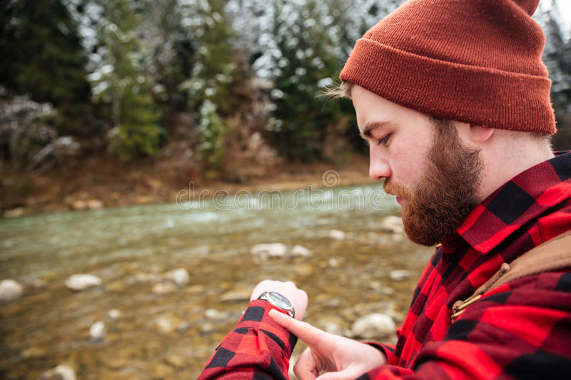 Man looking on the wrist watch outdoors. With river on background stock image