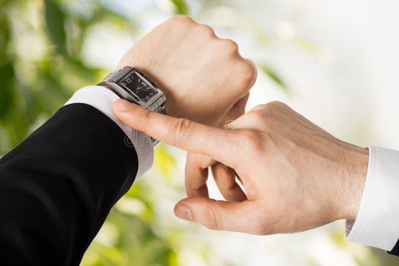 Man looking at wristwatch. Close up of man looking at wristwatch stock photos