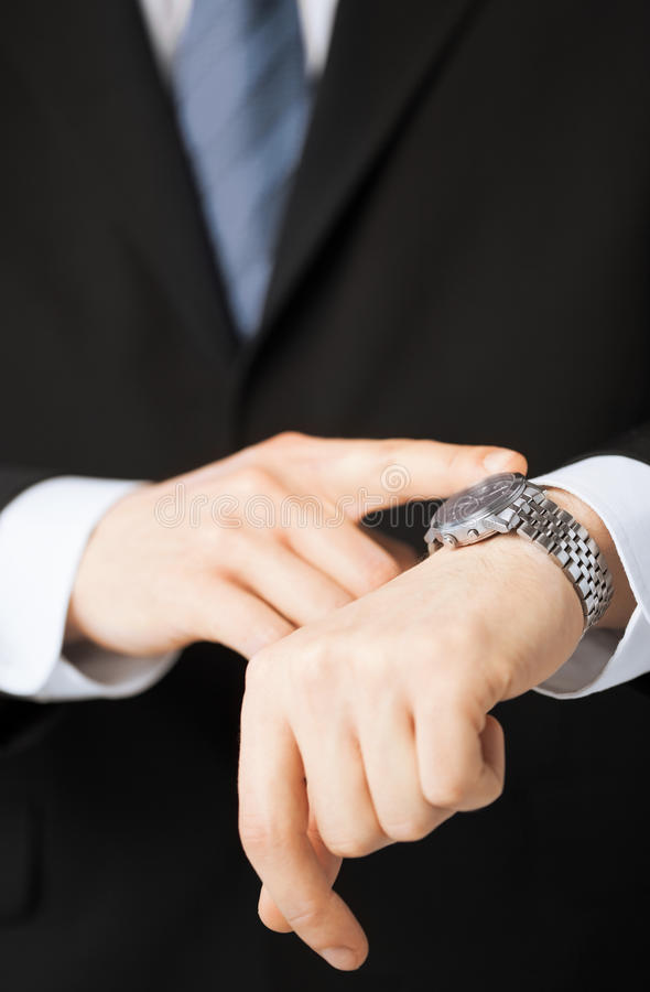 Man looking at wristwatch. Business people and office concept - close up of man looking at wristwatch stock image