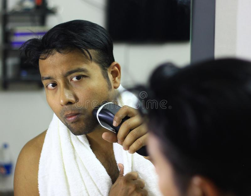 Man lookingIndian asian after his appearance in front of a mirror beauty styling lifestyle. Shaving routine stock images