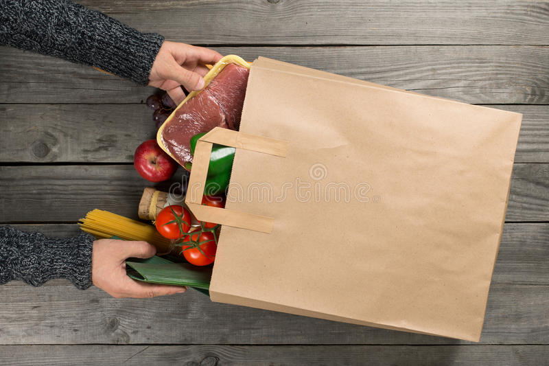 Man looks bag full of different healthy food. On wooden kitchen table, top view stock photo