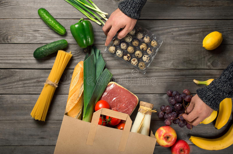 Man looks brown paper bag full of different healthy food. On wooden kitchen table, top view stock photos