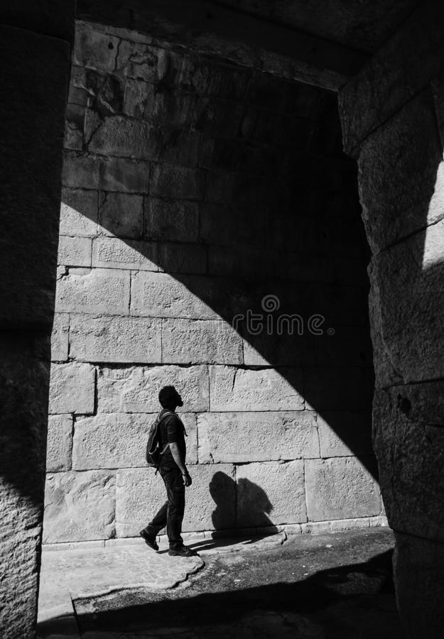 Man looks details of Bouleuterion wall in Patara Ancient City. Kas, Antalya, Turkey. Black and white art work. Light and shadow royalty free stock image