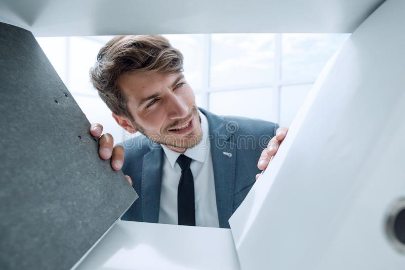 Man looks at documents in a closet. Pensive man looks at documents in a closet in the office stock images