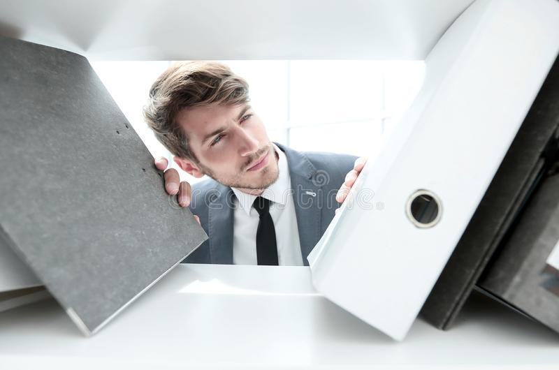 Man looks at documents in a closet. Pensive man looks at documents in a closet in the office royalty free stock image