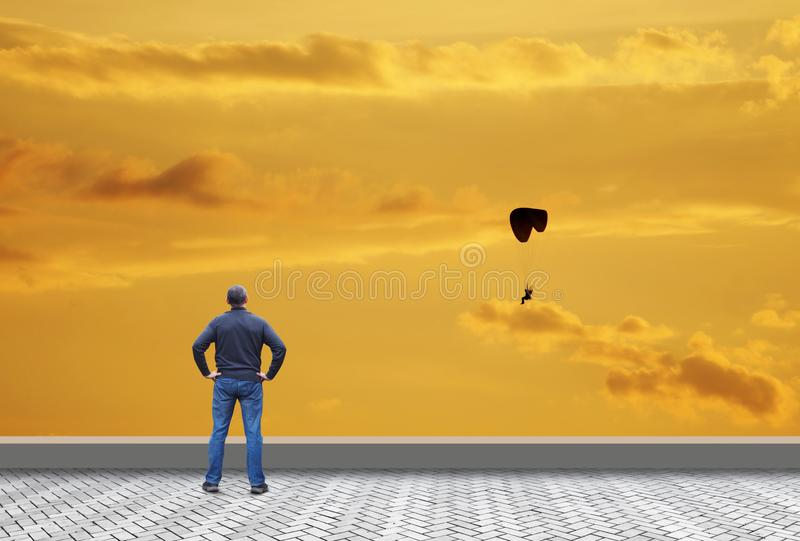 Man looks at a flying paraglider and want to fly stock image