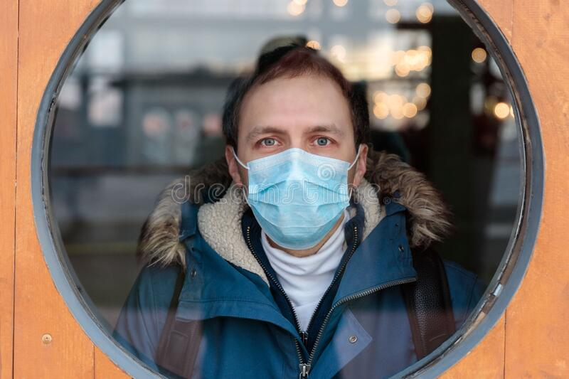 Man looks out the round window, wears protective medical mask. coronavirus, covid-19 pandemic, Quarantine. Man looks out the round window, wears protective royalty free stock image
