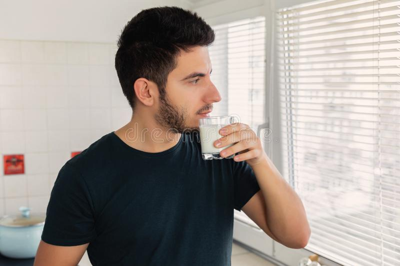 A man looks out the window early in the morning and drinks milk. Healthy lifestyle, healthy breakfast royalty free stock photo