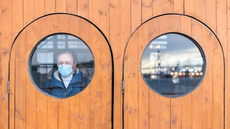 Man looks out the window, wears protective medical mask. coronavirus, covid-19, Life in isolation, quarantine. Man looks out the window, wears protective medical royalty free stock image